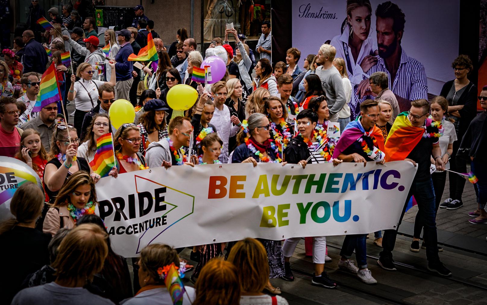 Iloisia ihmisiä Pride-kulkueessa.