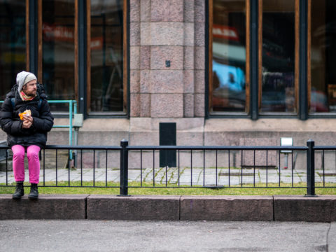 Mies istuu aidalla Helsingin keskustassa syömässä leipäannosta, kun maa taantumassa paniikkiin