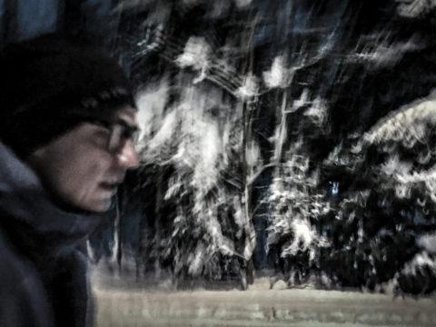 Mies juoksee pimeässä lumisessa metsässä